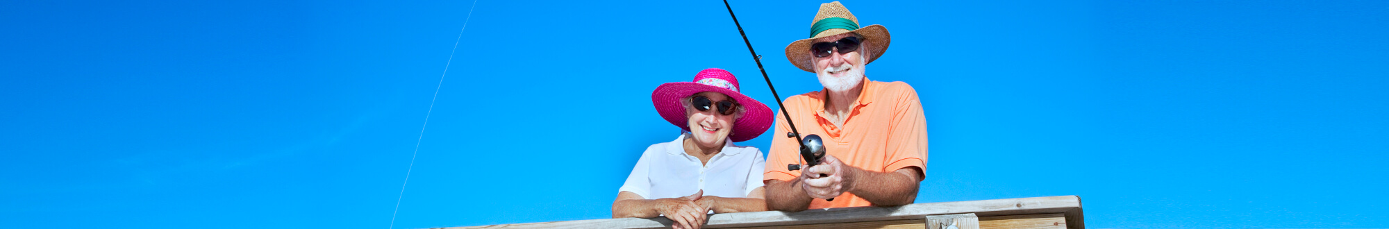 elderly couple wearing hat and sunglasses